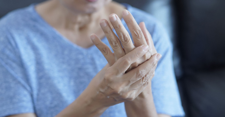 Photo of woman rubbing her hand due to arthritis pain