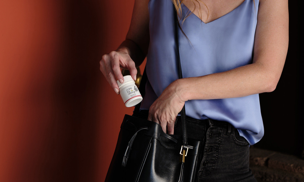 A woman pulling CBD soft gels from her purse
